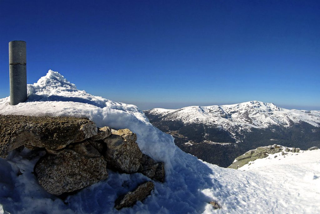Vértice Geodésico de Cabeza de Hierro Mayor (2382 m). Peñalara al fondo.